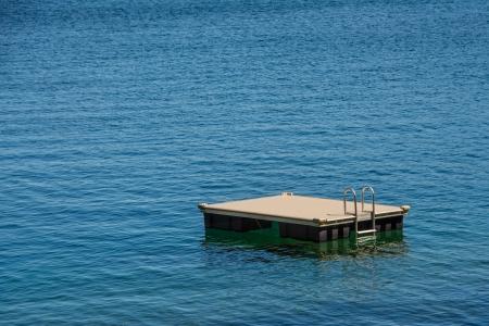 Empty swim platform floating on a lake