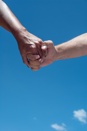 Man and women hands holding with blue sky backdrop