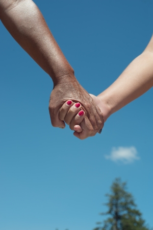 Male and female hands holding with blue sky background