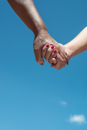 light and dark skin hand holding with blue sky Stock Photo