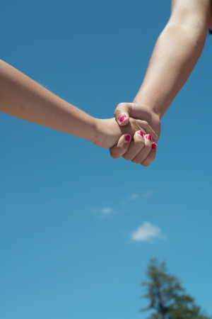 Close up of hand holding with blue sky
