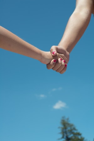 young male and female hand holding with blue sky Stock Photo