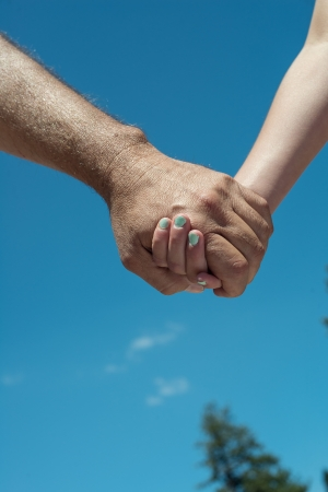 Man and young child holding hands with a blue sky background
