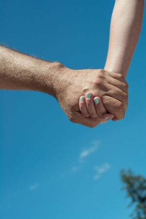 Father and daughter holding hands with blue sky background