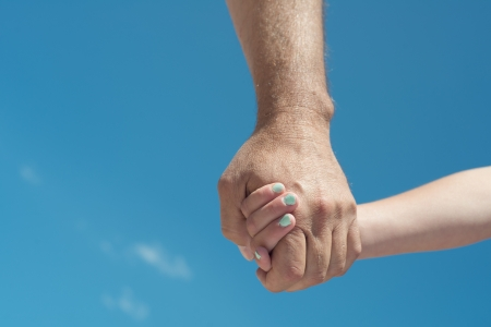 Man and child holding hands with blue sky background