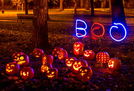 Halloween group of lit Jack O Lanterns at night in a park with the word BOO in lights behind them