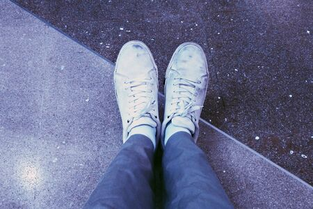 two tone: wearing dirty white sneakers with two tone granite floor in the background
