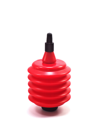 small black and red air dust blower made of plastic used for removing dust off camera lenses stand upright isolated on white background