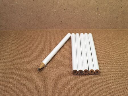 sharpened: six pencils with one pencil sharpened and five pencils unsharpened on wooden board Stock Photo