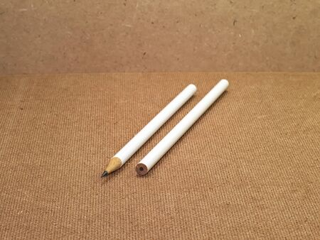 sharpened: two white pencils with one pencil unsharpened and one pencil sharpened on wooden board