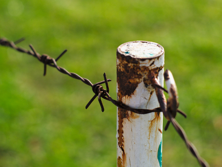 invade: rusty metal barbed wires on old and decayed metal pole