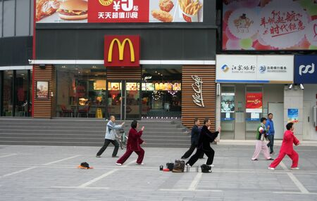 Shenzhen, China - March 1, 2015 - People practicing Tai Chi in front of a western fast food chain store in China