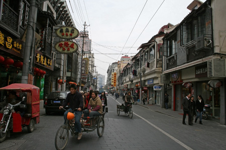 peddle: Shanghai, China - March 30, 2010 - A street view with bikes and pedi cabs Editorial