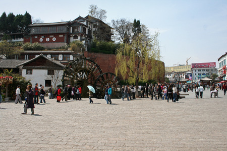 Tourists strolling around Lijiang water wheel and public square