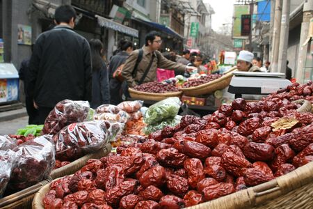 street vendor: Xiani, China - March 31 2011 - A man buying from a street vendor selling dried fruits and dates Editorial