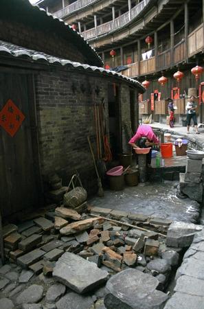 Yongdingi、中国 - 2010 年 7 月 14 日 - 女性家族の土楼の中の彼女の髪を洗う 写真素材 - 37796751
