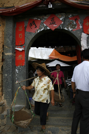 Yongdingi, China - July 14 2010 - A woman with a carrying pole leaves through the stone arch of anold Chinese building