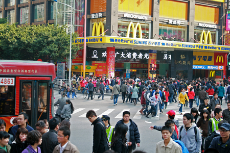 Shenzhen, China - January 15, 2011 - Large crowds of people moving past a McDonalds Store in China