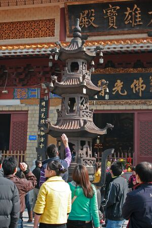 Shenzhen, China - January 8, 2011 - People gathered around an urn tower throwing coins for good luck