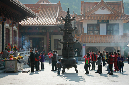 Shenzhen, China - January 8, 2011 - People gathered around an urn at Hongfa Temple Editorial