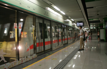 Shenzhen, China - August 8, 2012 - A metro train pulls into the station with a man in long pants and short sleeve waiting Editorial