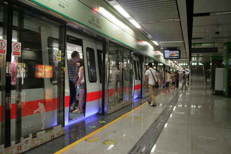 long pants: Shenzhen, China - August 8, 2012 - A man in long pants and short sleeve boards the Metro train in Shenzhen