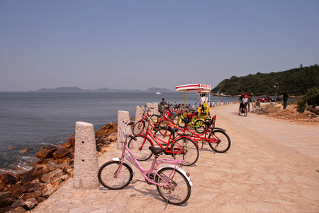 Shenzhen, China - March 26, 2012 - Rental bikes parked by the ocean at Yang Mei Keng Editorial