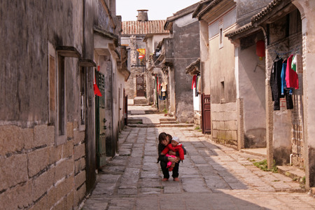 Shenzhen, China - March 27, 2012 - A mother and baby resting on a stone path inside Dapeng Ancient city 報道画像