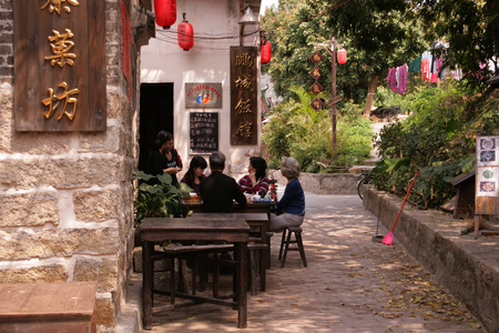 Shenzhen, China - March 27, 2012 - People dining in an outdoor garden setting within Dapeng Ancient city