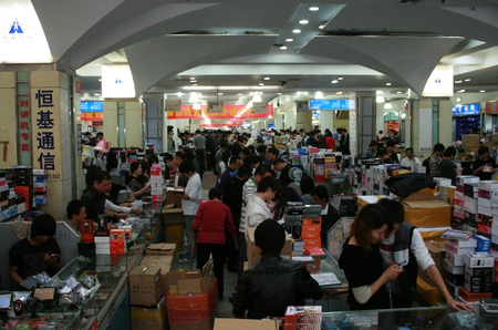 Shenzhen, China - December 20, 2010 -  A mobile phone market in Huaqiangbei packed with stalls and shoppers buying tablets and smartphones