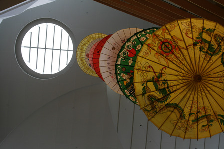 skylights: Chinese umbrellas hanging down from the roof beside a skylight