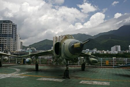 mig: Shenzhen, China - June 30, 2010 - A retired MIG fighter jet sits on top of of retired aircraft carrier(Minsk) in China Editorial