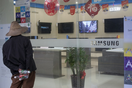 Shenzhen, China - January 20, 2015 - A man looks through the window of a Samsung retail store in China Editorial