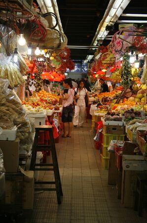 Hong Kong, China - October 25, 2010 -  A lady walking down the isle of Sheung Shui market, a local produce market