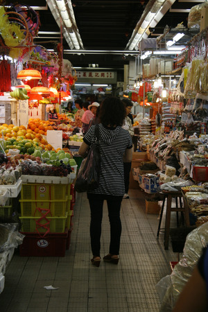 Hong Kong, China - October 25, 2010 -  A lady stands with her back to camera in an isle of Sheung Shui market, a local produce market