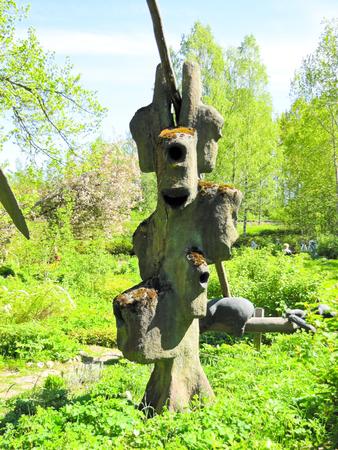 tallado en madera: divertidas figuras de madera y de piedra sobre un fondo de árboles Foto de archivo