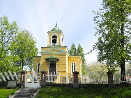 beliefs: wooden Church in yellow on a blue sky background Stock Photo