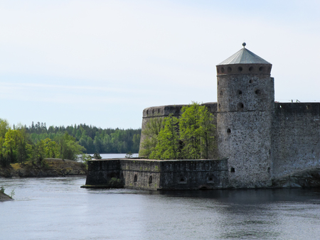 old castle by the river on a background of forest and blue sky Editorial