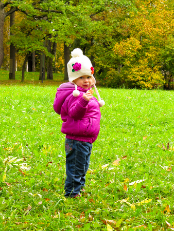 smiling girl in a white hat on a background of green meadows