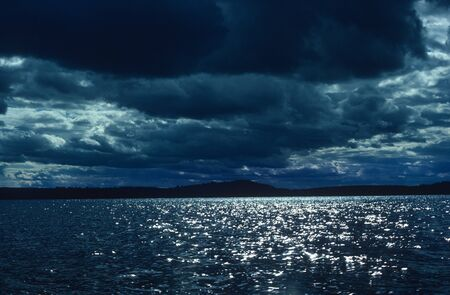 Dark Clouds Over Sparkling Waters Stock Photo