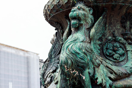 close up bronze griffin at the flower pot. His eyes are looking to the sky of Venice, Italy Stock Photo