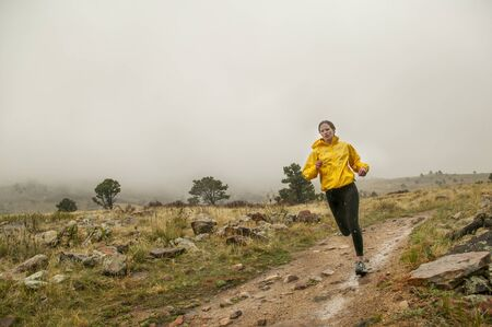 Red headed woman in yellow on rainy day run.