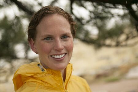 dominant color: Red headed woman in yellow on rainy day run. Stock Photo