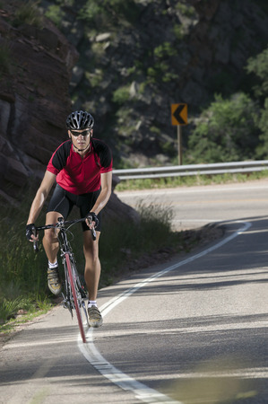 able: Fit male bicyclist wearing red jersey riding mountain road.