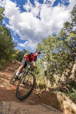 dominant color: Mountain Biker in red jersey from low wide angle with trees, rocks, blue sky and white clouds.