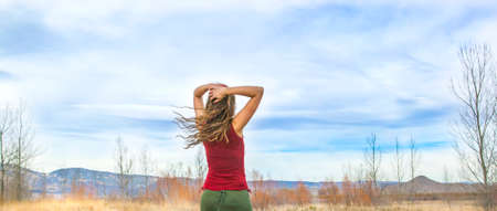millennial: Young woman in red top walking on beautiful fall day in rural setting. Stock Photo