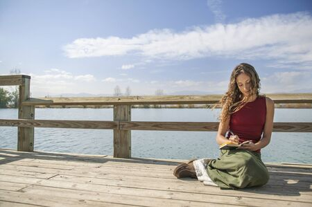 dominant woman: Beautiful long haired woman writing in journal near rural lake.