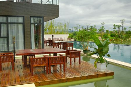 garden furniture: House patio with wooden table and swimming pool