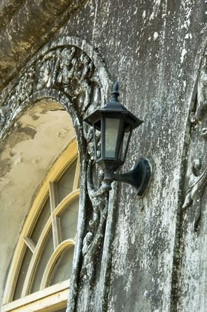 old street lamp on a sculpted wall photo