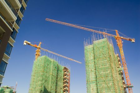 Large crane over some buildings in construction, viewed from a new finished residential district. Stock Photo - 3342039